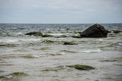 Stormy sea beach with large rocks in the wet sand. Baltic sea royalty free stock photos