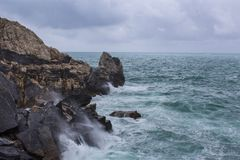 Stormy sea with big waves and black rocks royalty free stock photos