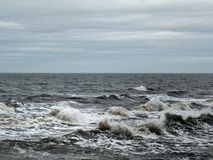 Stormy sea with dark waves and surf with a grey winter sky Royalty Free Stock Photo