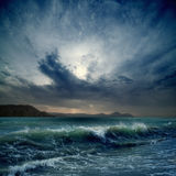 Stormy sea. Dramatic landscape - dark stormy sky, sea waves, mountains Royalty Free Stock Image