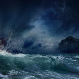 Stormy sea. Dramatic nature background - big wave and dark rock in stormy sea, stormy weather stock images