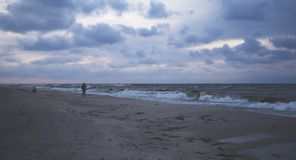 A stormy sea and a man on the shore Stock Image