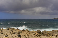 Stormy sea at stony shore. With dark clouds in the back Stock Photography