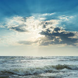 Stormy sea and sun in dark clouds Stock Photos