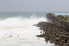 Stormy sea during typhoon, waves crashing on barrier wall Stock Photo