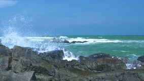 Stormy sea and water waves splashing on rocky beach on blue sky landscape. Water waves breaking on stony coast in ocean. Blue sea crushing a rocky cliff on sky stock video footage