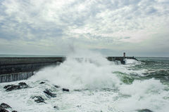 Stormy sea waves crushed over pier with lighthouse in Porto, Portugal Stock Photos