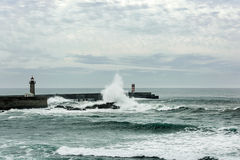 Stormy sea waves over lighthouse in Porto, Portugal. Stormy sea waves crushed over pier with lighthouse in Porto, Portugal Royalty Free Stock Photo