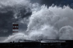 Stormy sea waves over pier and lighthouse Stock Photo
