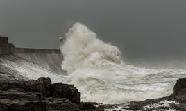 Stormy seas battering a loght house. Storm callum battering south wales coast at Porthcawl beach light house behind the waves royalty free stock photography