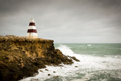 Stormy Seas. Beacon on a cliff top with waves crashing underneath a stormy sky stock images