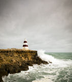 Stormy Seas. Beacon on a cliff top with waves crashing underneath a stormy sky stock photography