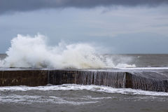 Stormy seas break over the sea wall at the Long Hole in Bangor, County Down during rough seas in a storm in January 2017. This old harbor is avital part of royalty free stock photography