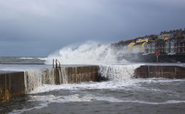 Stormy seas break over the sea wall at the Long Hole in Bangor, County Down during rough seas in a storm in January 2017. This old harbor is avital part of stock photography