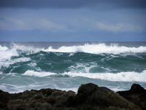 Stormy Seas. A seascape of stormy clouds and waves on a rocky shoreline stock photography