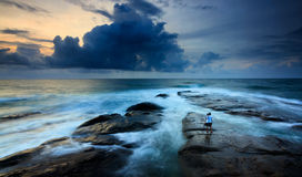 Stormy seascape with lone photohrapher at the Tip of Borneo, Malaysia Royalty Free Stock Photos