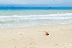 A baby drawing on the sand at the bech alone, Vietnam, Nha-trang. Stormy Seascape with sweet children Stock Photos