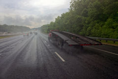 Stormy Semi Truck on Highway. Rear and side view of semi truck on highway under stormy sky Stock Image