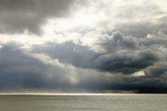 Stormy Skies over Sea. Dark clouds forming stormy sky above the sea Stock Photos