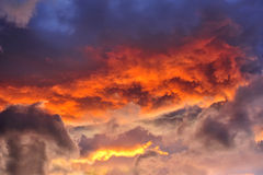 Stormy skies at sunset. A jumble of stratocumulus clouds at sunset. Suitable as an abstract, natural graphics background Stock Photos