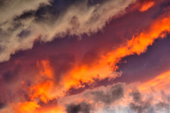 Stormy skies at sunset. A jumble of stratocumulus clouds at sunset arranged in lines with a diagonal composition. Suitable as an abstract, natural graphics Royalty Free Stock Images