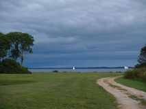 Stormy Sky Behind White Sail Boats. An intensive gray colored stormy sky is just above the ocean. A large meadow with a dirt road makes its way to the shoreline Stock Photography