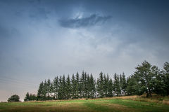 Dark sky over mountain and pines Royalty Free Stock Photo