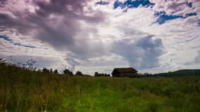 Stormy sky over a old barn - meadow. Stormy magical sky with moving colorful clouds over a old barn in a meadow stock footage