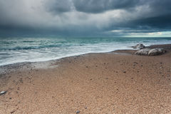 Stormy sky over rock beach in Atlantic ocean Stock Photo