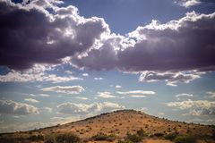 Stormy sky and promising rain clouds over a dry Kalahari desert hill royalty free stock image
