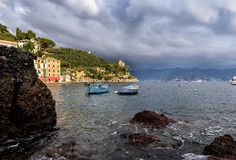 Stormy sky and small boats in sea bay of Portofino town. Portofino is small fishing town in Liguria district, Italy. Royalty Free Stock Photos