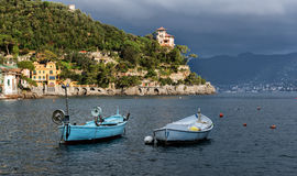 Stormy sky and small boats in sea bay of Portofino town. Portofino is small fishing town in Liguria district in Italy. Stormy sky and small boats in sea bay of Stock Photos