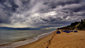 Stormy sky in a summer beach. A picture of a stormy sky over a beach,and deck chairs in the distance,in a greek town Nea Moudania,in a rainy day afternoon of Stock Image