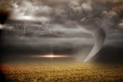 Stormy sky with tornado over field Stock Photos