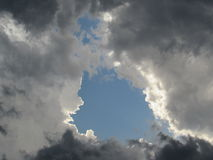 Stormy Sky with Turbulent Gray Clouds and Blue Sky Opening royalty free stock image
