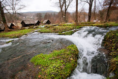 Stormy small river flowing from the ancient village with wooden houses Stock Photo