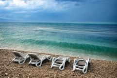 Stormy summer scene beach. Stormy scene with rough sea waves by empty beach loungers royalty free stock photos