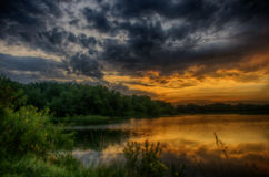 Stormy Sunrise over a lake. Royalty Free Stock Images
