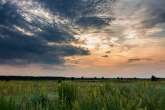 Stormy sunset. Dramatic stormy sky above wild field. Sunset Royalty Free Stock Photography