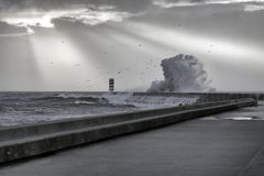 Stormy sunset with sunbeams. South pier and beacon of Douro river mouth during winter seeing big dangerous wave splash Stock Photography