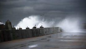 Stormy surf breaking on breakwater. Against dark clouds stock photos