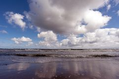 Stormy surf by daytime. Stormy surf at the Baltic sea and white clouds above by daytime Stock Photography