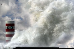 Stormy wave. Storm waves over beacon of the harbor of Douro, Portugal - enhanced sky Royalty Free Stock Image