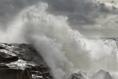 Stormy wave crashing over rocky coast Royalty Free Stock Images