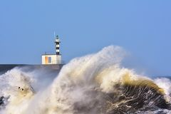 Stormy wave over lighthouse of San Esteban de Pravia. Royalty Free Stock Images