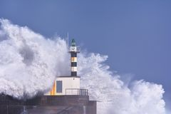 Stormy wave over lighthouse of San Esteban de Pravia. Royalty Free Stock Photo