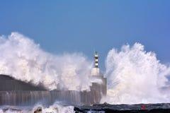 Stormy wave over lighthouse of San Esteban de Pravia. Stock Photo