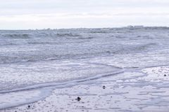 Stormy waves with foam in the sea. Sand beach in winter. Stormy waves with foam in the sea. Sand beach in winter royalty free stock photography
