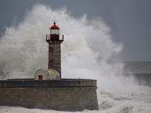 Stormy waves over old lighthouse Stock Image