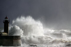 Stormy waves over old lighthouse and pier Stock Photos